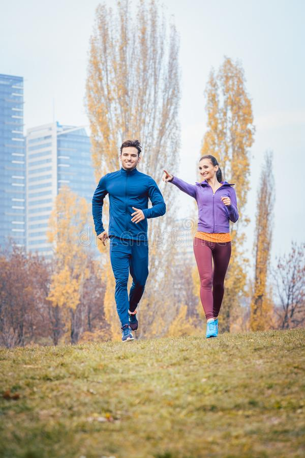 Urban jogging - couple running in autumn city royalty free stock photo