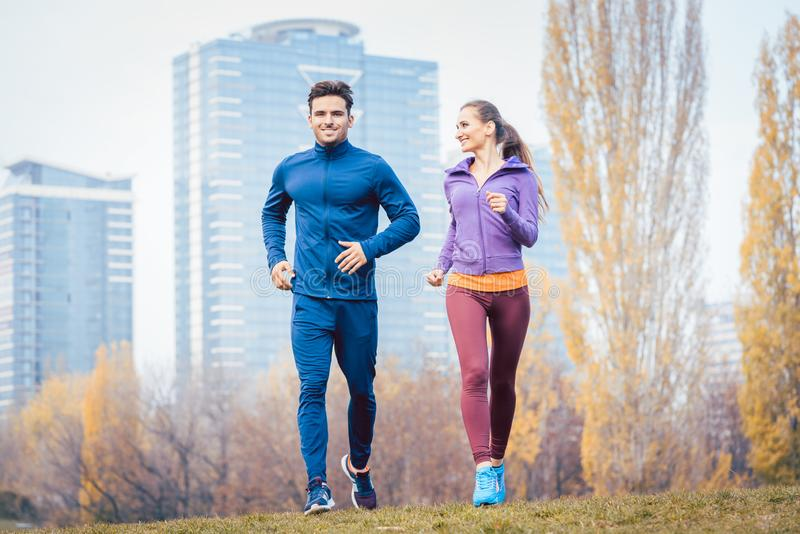 Urban jogging - couple running in autumn city stock images