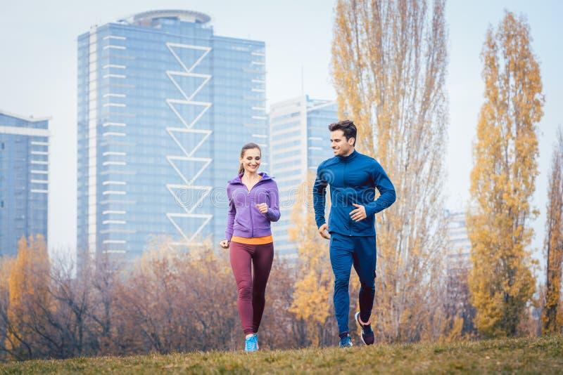 Urban jogging - couple running in autumn city stock photo