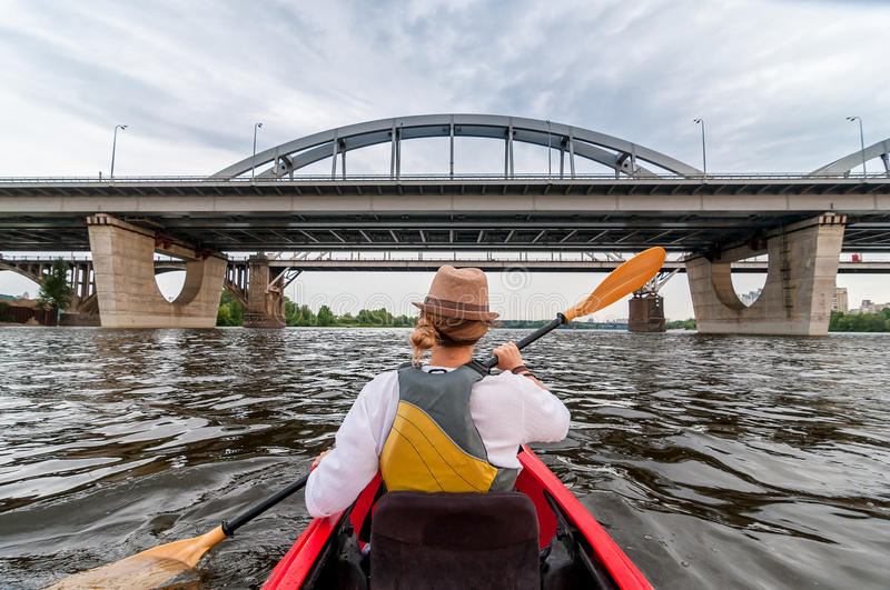 Urban kayaking travel by the river. Beautiful young girl at red kayak or canoe swims towards the bridge. Weekend summer royalty free stock image