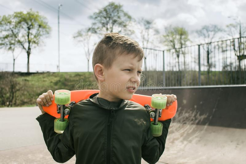 Urban kid boy with a penny skateboard stock photo