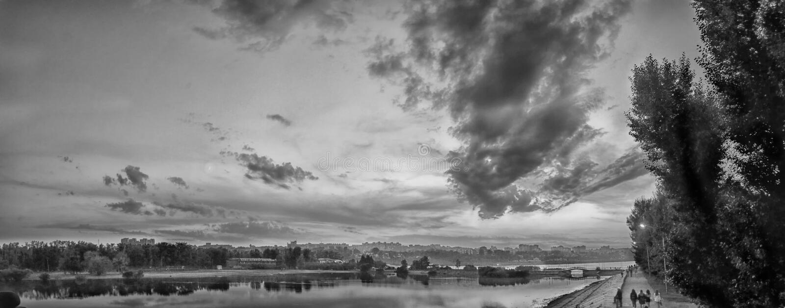 Urban landscape. Embankment of the Angara river at sunset. The moon and the Sun. Russia, Irkutsk. Black and white image. Panorama. Autumn royalty free stock images