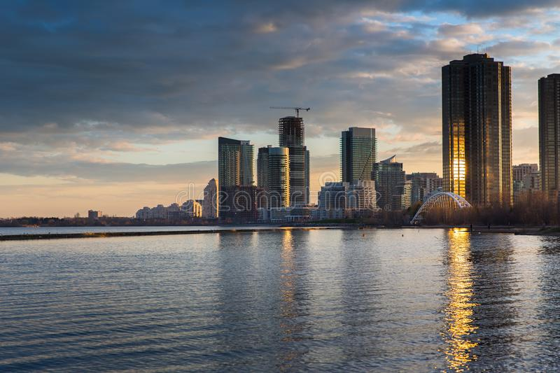 Urban landscape with high-rise buildings lake view. During sunset wit dramatic clouds and lake reflections royalty free stock photos