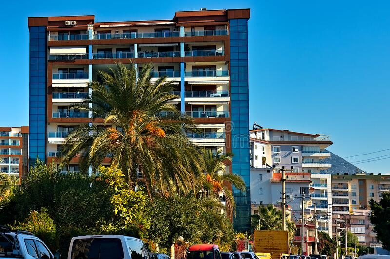 Urban landscape with modern house and date palm. Multi-storey house over a busy street in the Mediterranean stock image