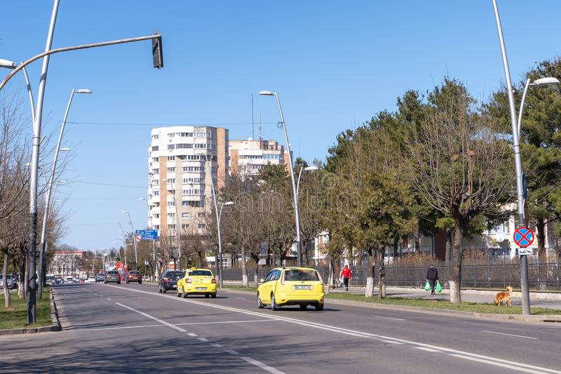 Urban life in Bacau, a city in north-east Romania, with cars on the street and people walking on the sidewalk. BACAU, Romania - March 23 2019: Urban life in royalty free stock image