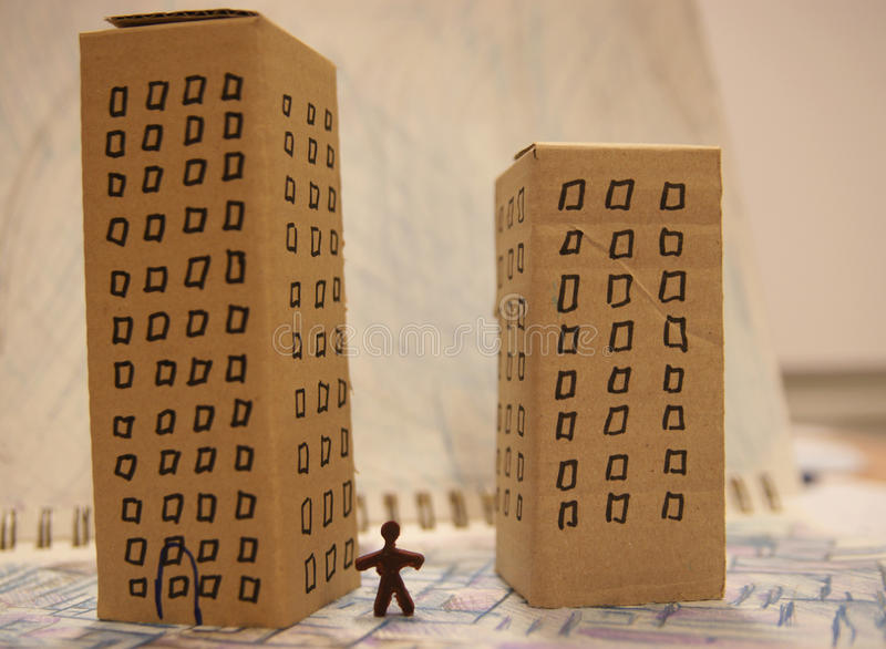 Urban life. Cardboard houses and tiny toy figure stock image