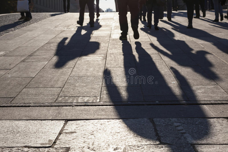 Urban life concept, people shadows on streets. People shadows on streets in sunset, urban city life concept image, anonymous group of humans royalty free stock image