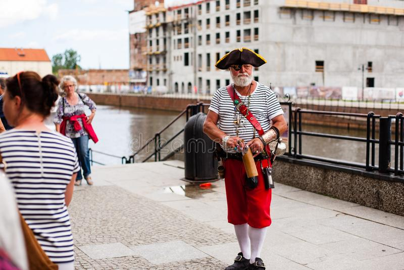 Urban life. Old man dressed as pirate in A Big City Street royalty free stock photography