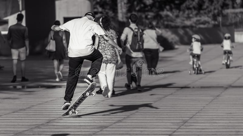 Urban life. With people walking, cildren cycling and a skater jumping stock images