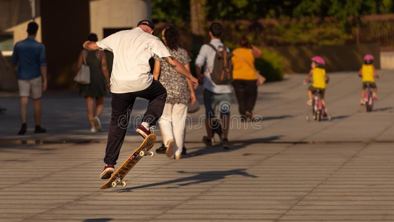 Urban life. With people walking, cildren cycling and a skater jumping stock photography