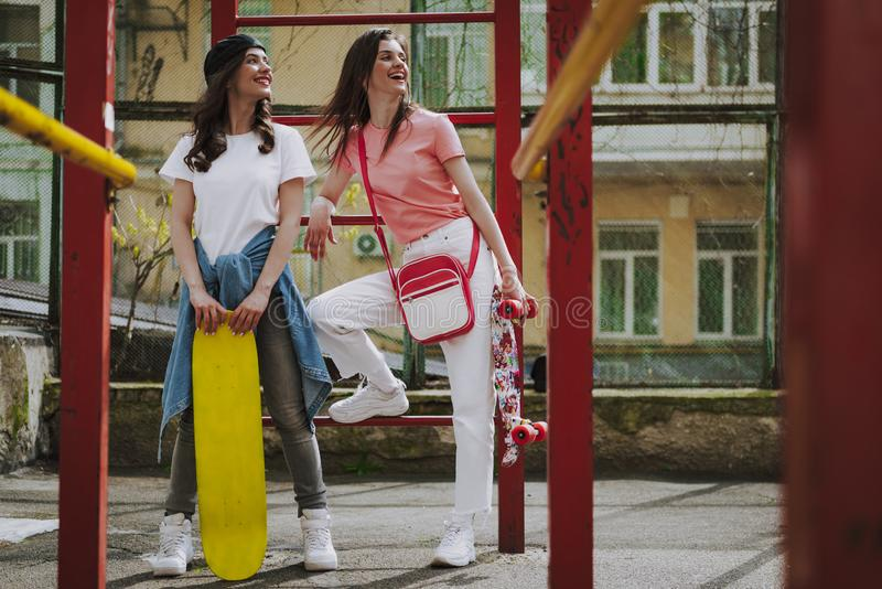 Young happy hipster girls staying with skateboards. Urban lifestyle and activity concept. Full length portrait of happy smiling hipster ladies with skateboards stock photo