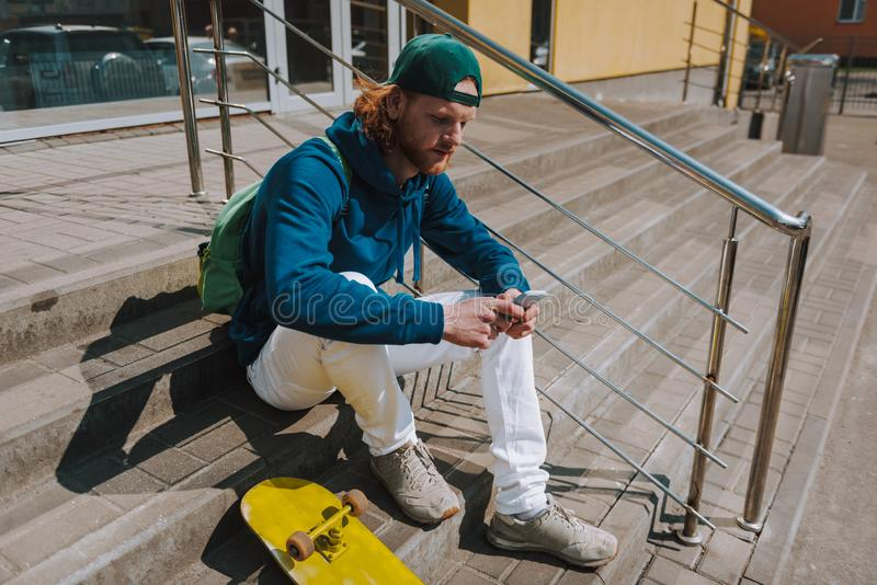 Skater man messaging on mobile phone on stairs. Urban lifestyle and activity. Full length portrait of young hipster guy sitting on stairs outdoor with skateboard stock images