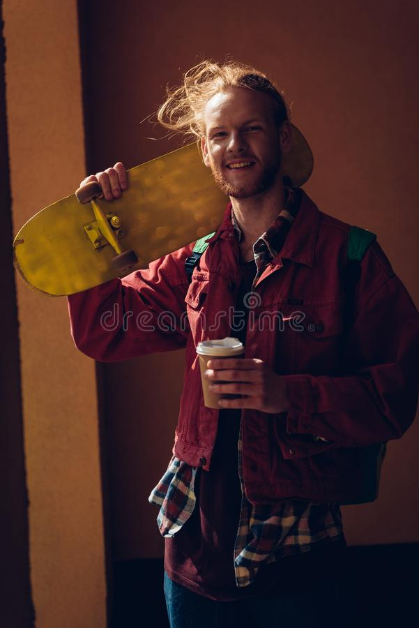 Smiling skater man with coffee and skateboard. Urban lifestyle and activity. Waist up portrait of happy young hipster guy staying on sun light with yellow royalty free stock photos