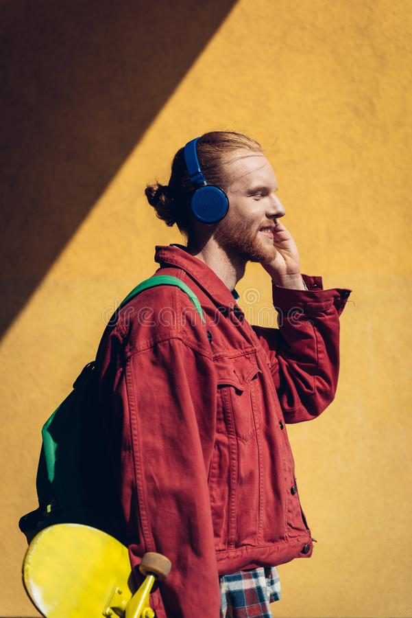 Happy skater man listen to music via headphones. Urban lifestyle and activity. Waist up side on portrait of young smiling hipster guy with yellow skateboard stock image