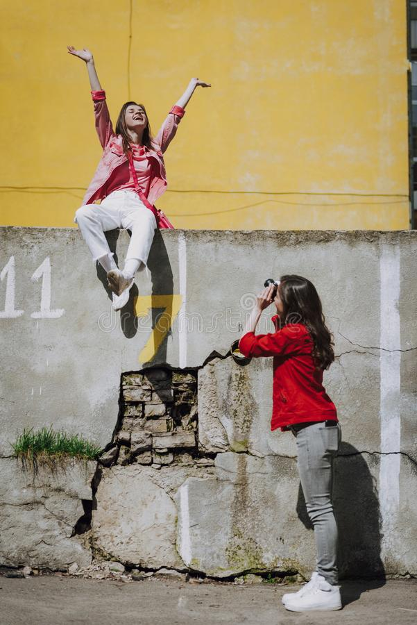 Young lady making photo of happy hipster girl. Urban lifestyle concept. Full length side on portrait of young women making photo of happy excited hipster girl stock images
