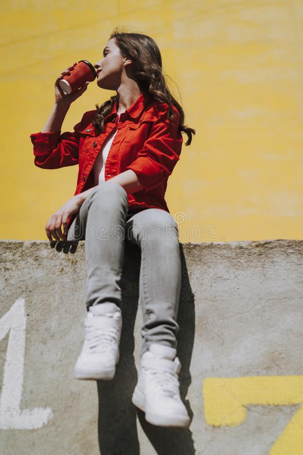 Young hipster girl drinking coffee on parapet royalty free stock image