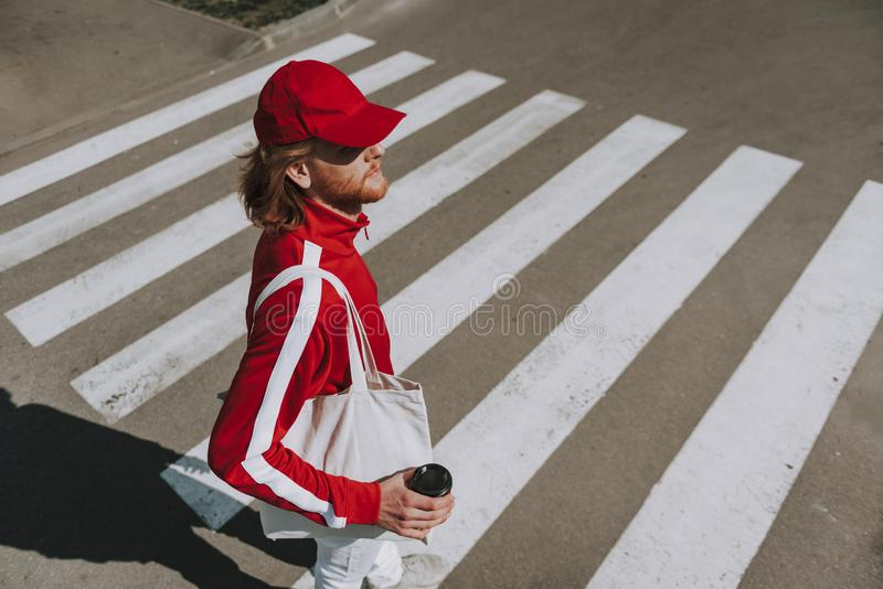 Young hipster man with coffee on crosswalk. Urban lifestyle concept. Top angle waist up portrait of young hipster man with cup of coffee and white eco bag royalty free stock photos