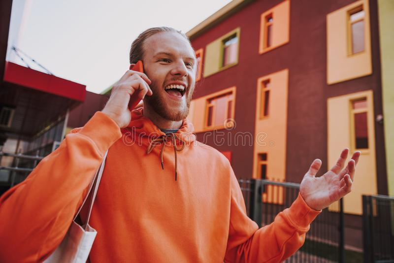 Happy hipster man talking by phone on walk. Urban lifestyle concept. Waist up low angle portrait of young happy hipster man in red fleece talking by mobile phone stock image