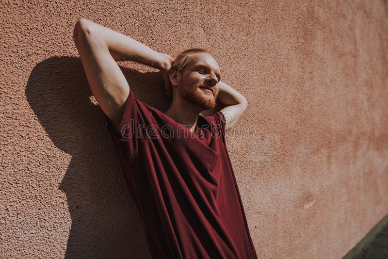 Young relaxed hipster man leaning on building. Urban lifestyle concept. Waist up low angle portrait of young smiling hipster guy relaxed leaning on building wall royalty free stock photography
