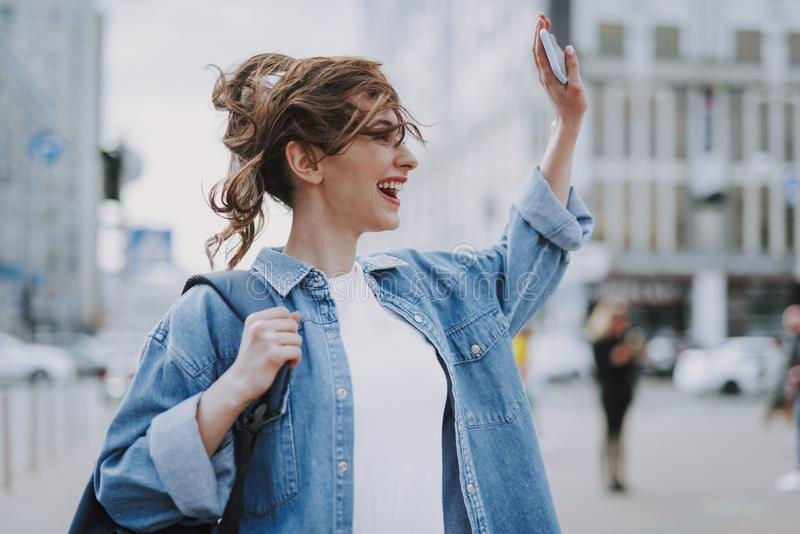 Pretty happy young female greeting to somebody royalty free stock image