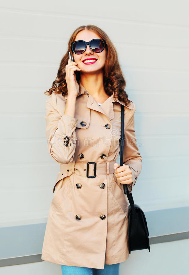 Urban lifestyle fashion portrait smiling young woman talking on smartphone wearing a coat and handbag clutch stands over grey. Background stock images