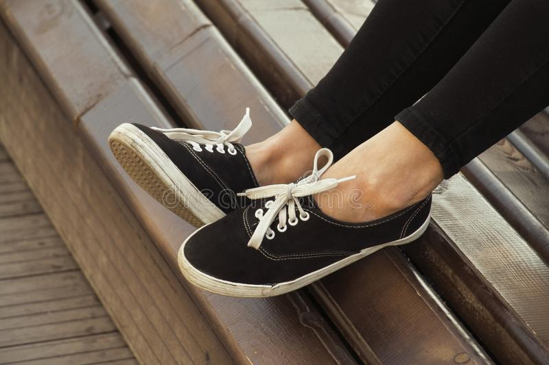 Urban lifestyle. Female legs in sneakers on the bench stock photos