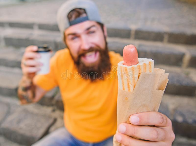 Urban lifestyle nutrition. Carefree hipster eat junk food while sit on stairs. Hungry man snack. Junk food. Guy eating. Hot dog. Man bearded bite tasty sausage stock photography