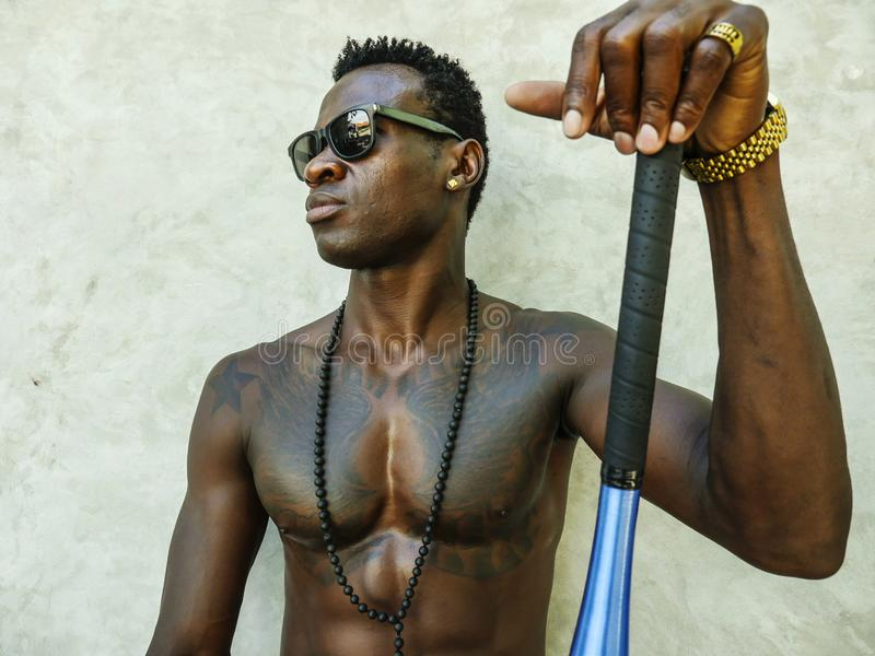 Young attractive and handsome black afro American man with fit muscular body and six pack holding baseball bat posing cool badass royalty free stock photo