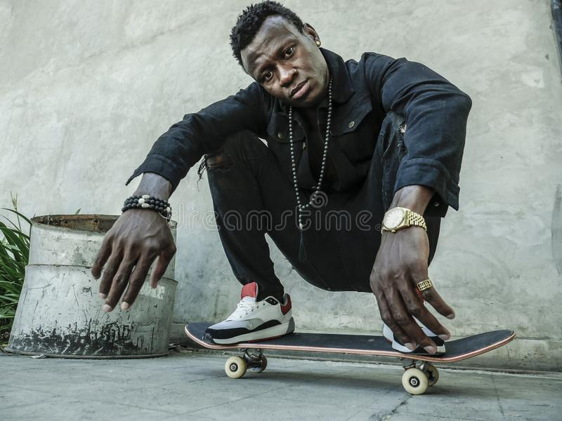 Young attractive and serious black African American man squatting on skate board at grunge street corner looking cool posing in. Urban lifestyle portrait of royalty free stock image