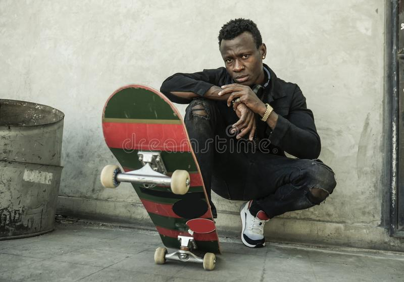 Urban portrait of young attractive and serious black afro American man with skate board squatting on street corner looking cool royalty free stock photography