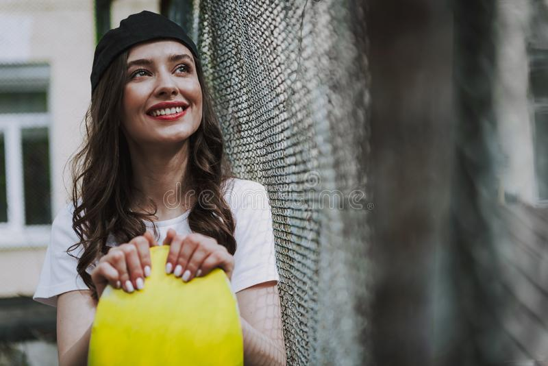 Pretty happy hipster girl with yellow skateboard. Urban lifestyle and sport activity. Close up portrait of young pretty smiling hipster lady holding yellow stock photography