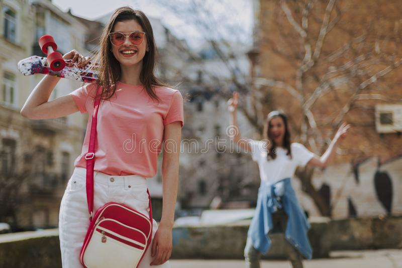 Waist up happy hipster girl with penny board. Urban lifestyle and sport activity. Waist up low angle portrait of young pretty smiling hipster lady staying with stock photo