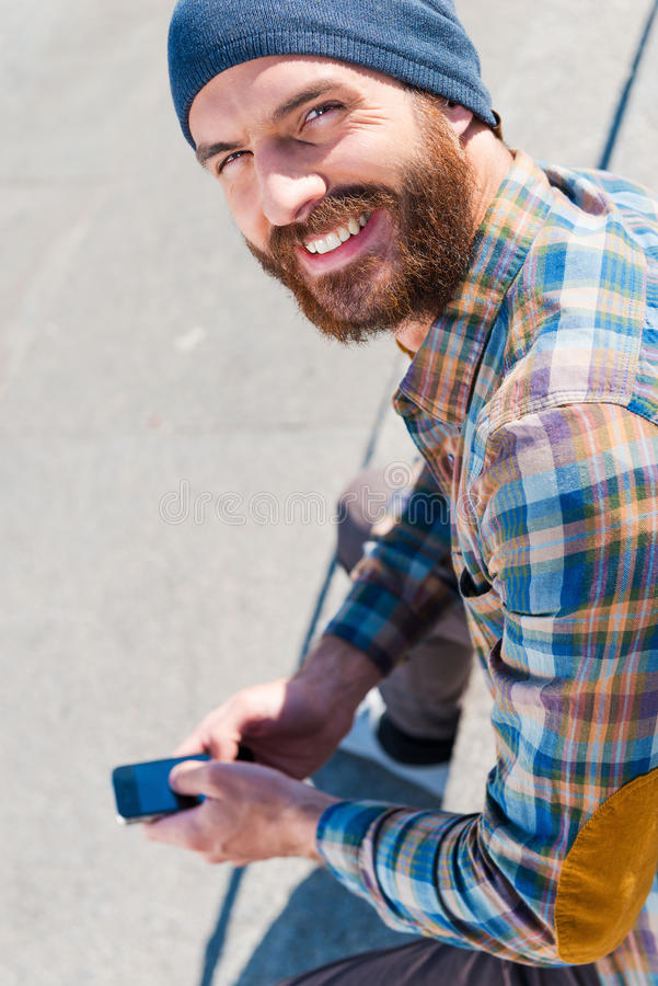 Urban lifestyle. Top view of handsome young man sitting and writing a message stock image