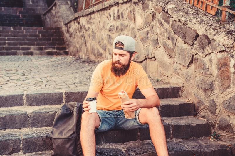 Urban lifestyle and unhealthy nutrition. Carefree hipster eat junk food while sit on stairs. Hungry man snack. Junk food stock image