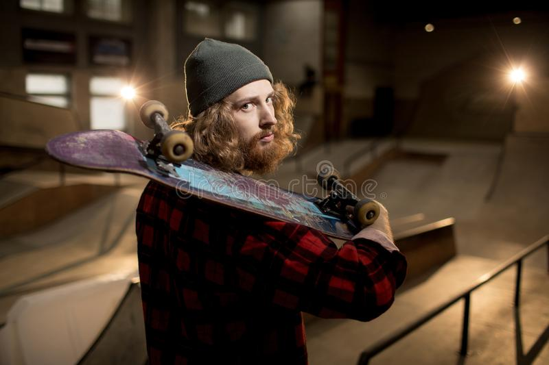 Urban Lifestyle. Waist up portrait of long haired man holding skateboard looking at camera standing in extreme park, shot with flash stock photo
