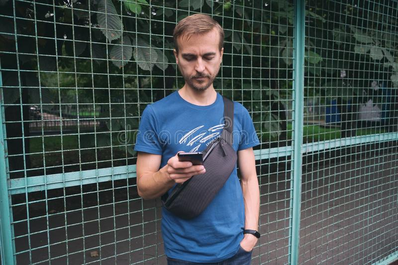 Urban lifestyle. Young bearded man in blue t-shirt with crossbody bag staying near fence of city sport playground and using royalty free stock image