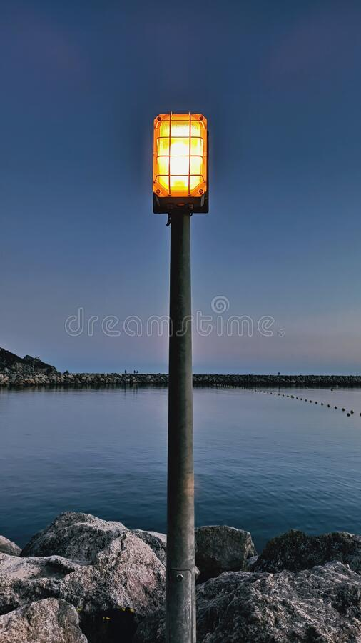 Urban light in the rocky dock against blue sea at sunset royalty free stock images