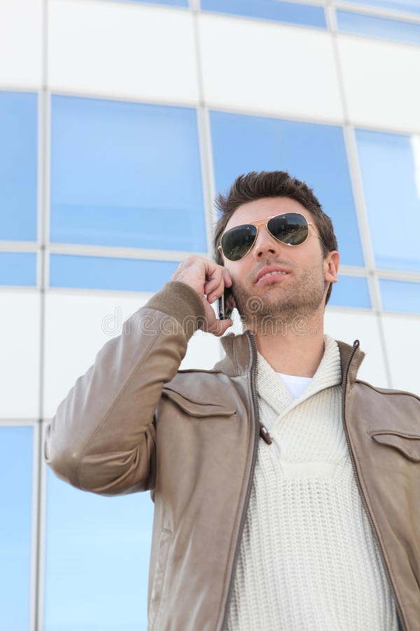 Urban man in aviators. With a mobile phone stock images