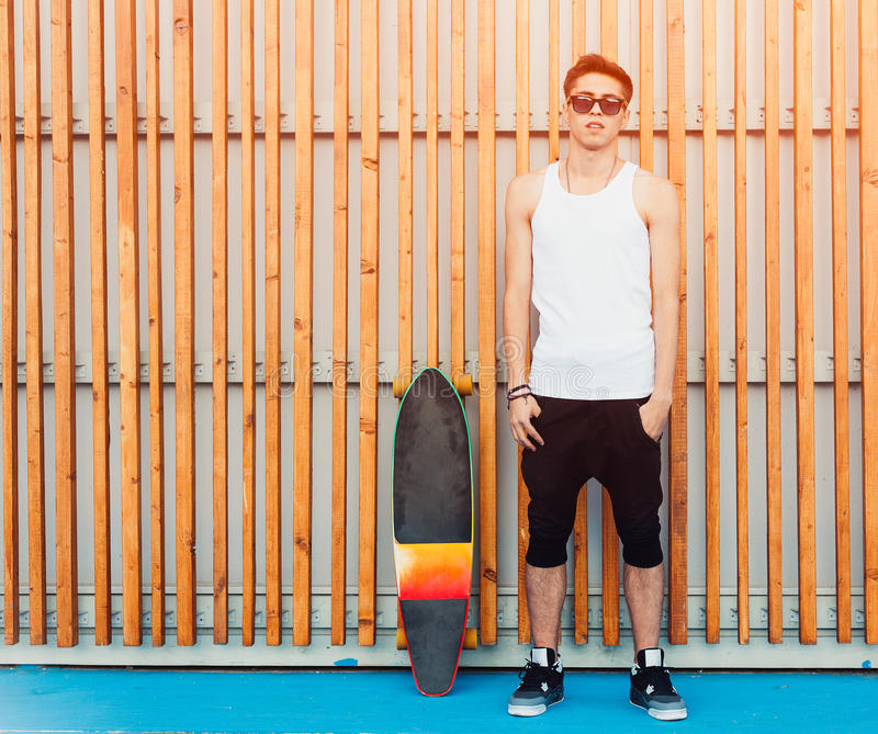 Urban man sunglasses and skateboard posing on wood planks background. Good looking. Cool guy. Wearing white shirt and black. Pants. Outdoor stock photos