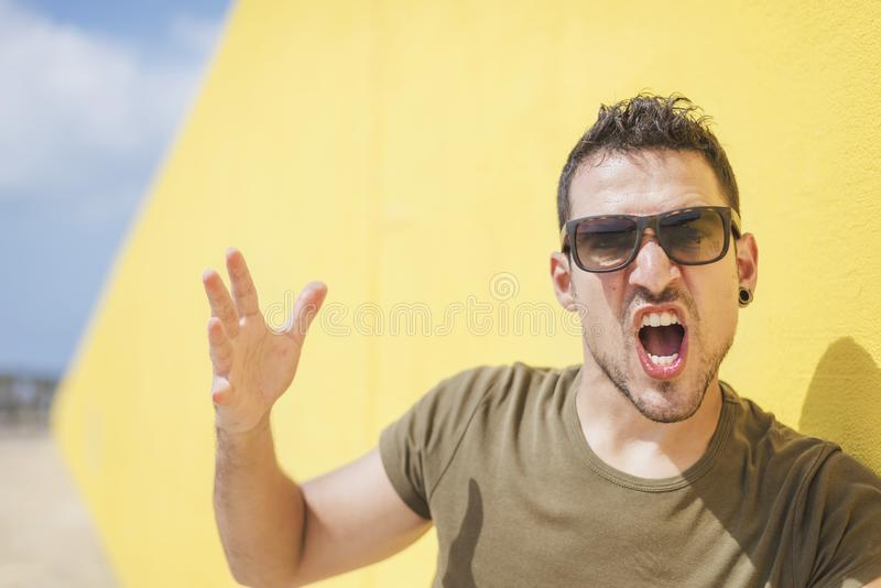 Urban man wearing sunglasses shouting to you royalty free stock images