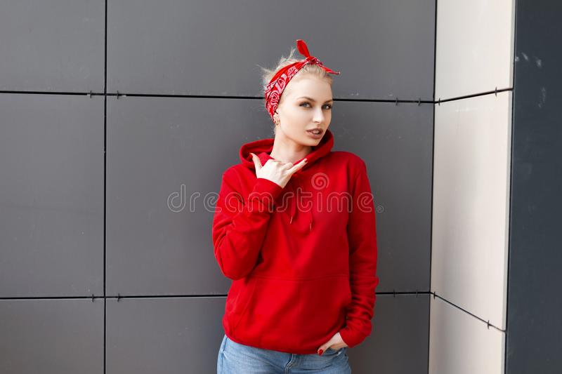 Urban modern pretty young woman in a fashionable red sweatshirt in a red stylish bandana in blue jeans posing in a city stock photo