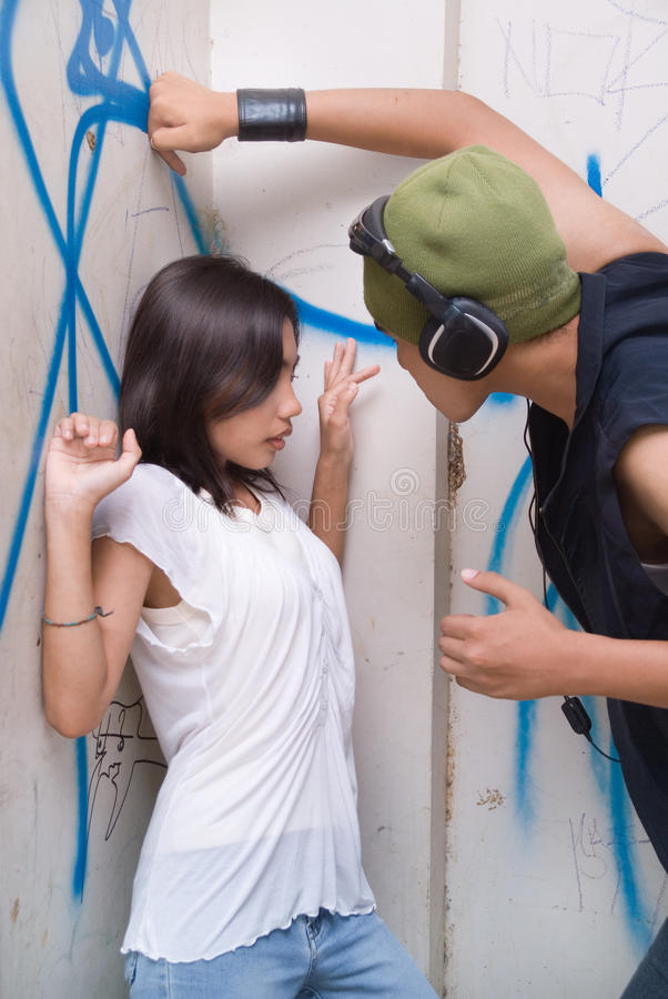Urban mugger intimidating girl. Young tough Hispanic grunge gangsta mugger with headphone and cap intimidating a cornered and frightened girl in an urban slum stock images