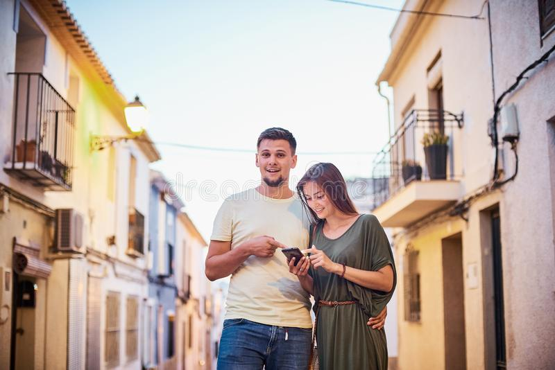 Urban photo of young adult couple looking at cellphone stock image