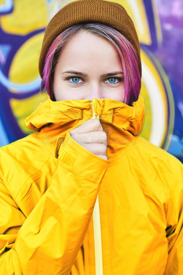 Urban portrait cool young woman in yellow jacket and knitted hat posing against wall painted with graffiti. royalty free stock photos