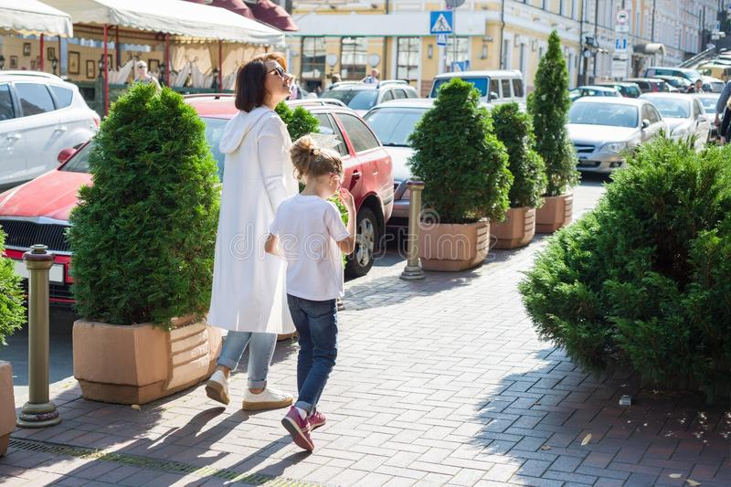 Urban portrait of parent and child. Mother and daughter hold hands, walk around the city, back view. royalty free stock photography