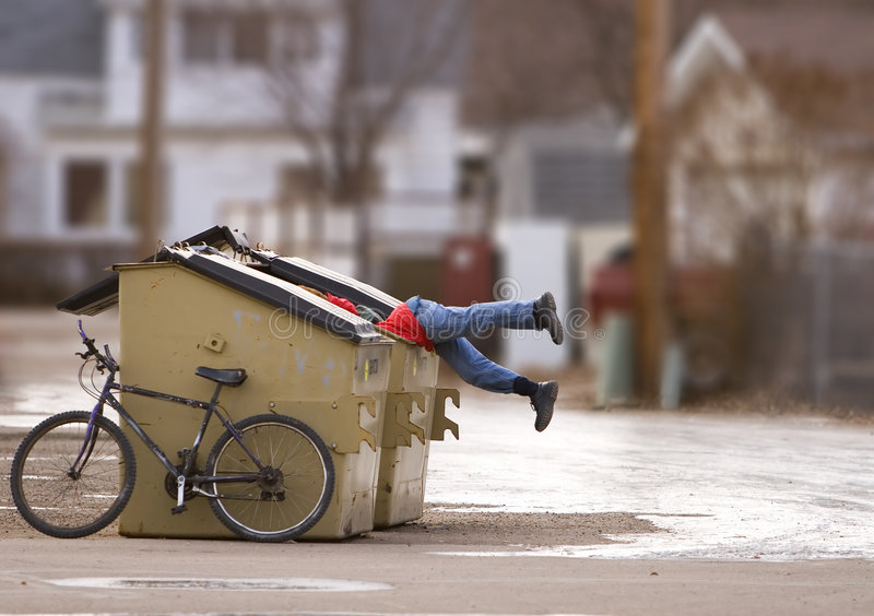 Urban poverty. Man with a bike looking in a dumpster