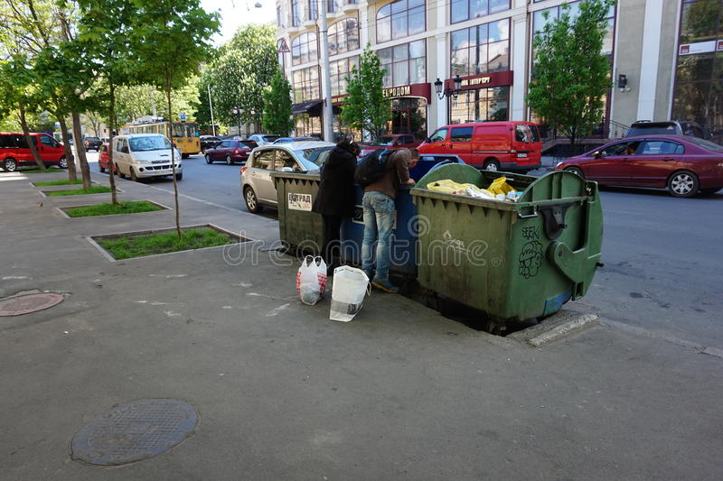 Urban Poverty. A homeless people looking for food in a garbage dumpster royalty free stock photography