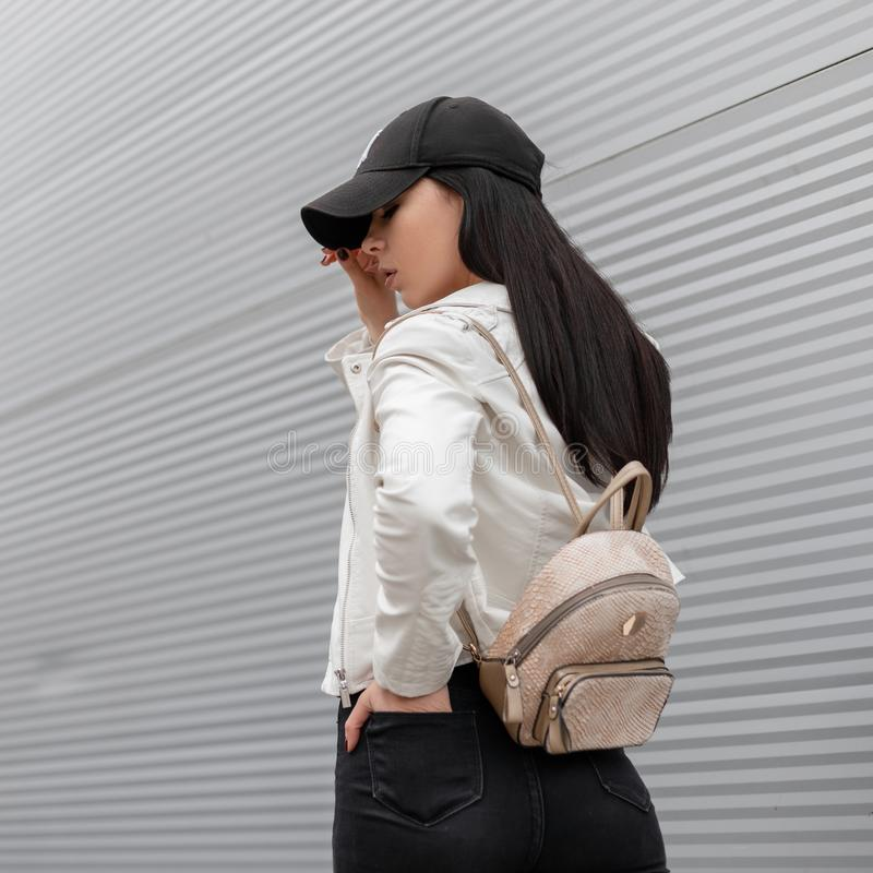 Urban pretty young woman in a fashionable white leather jacket with a vintage backpack in a trendy baseball cap walks stock image