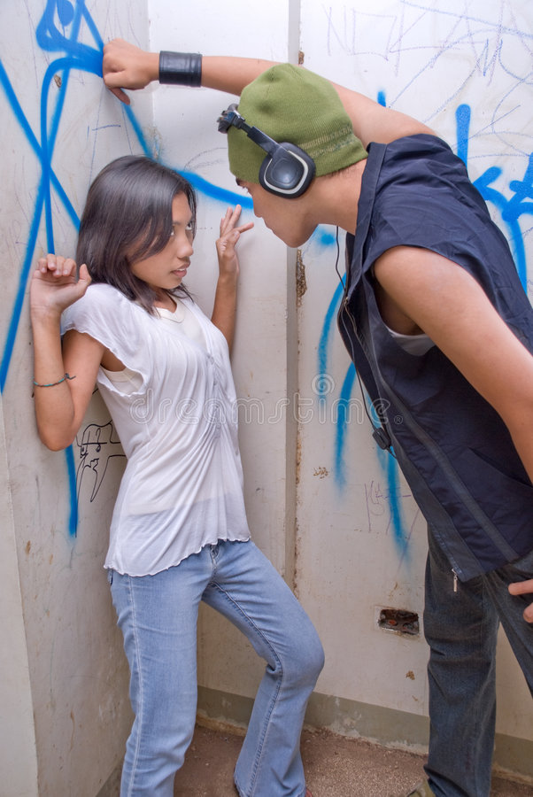 Urban rapper intimidating girl. Young tough Asian male rapper with headset and cap intimidating a cornered and frightened girl in an urban environment with stock photos