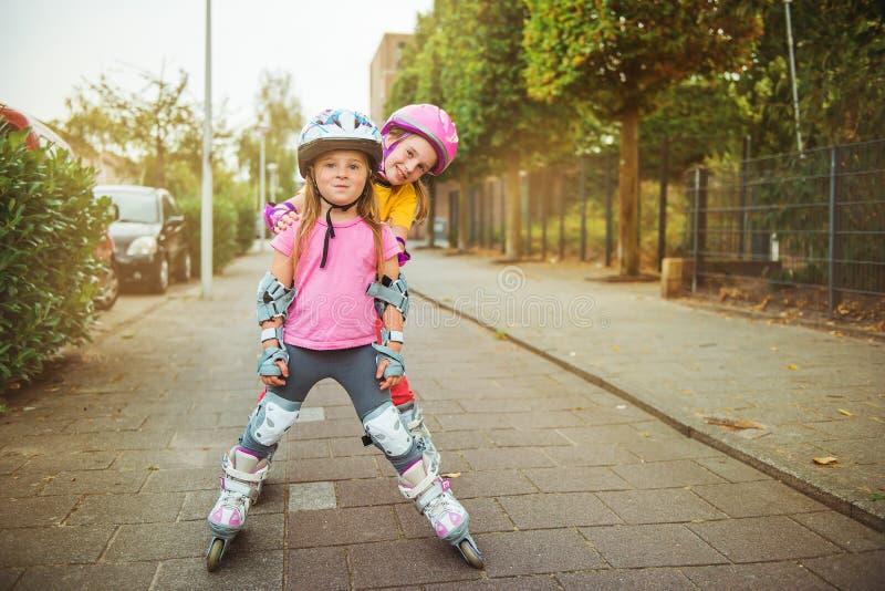 Urban roller skating. Active excited kids trying urban roller skating stock photos